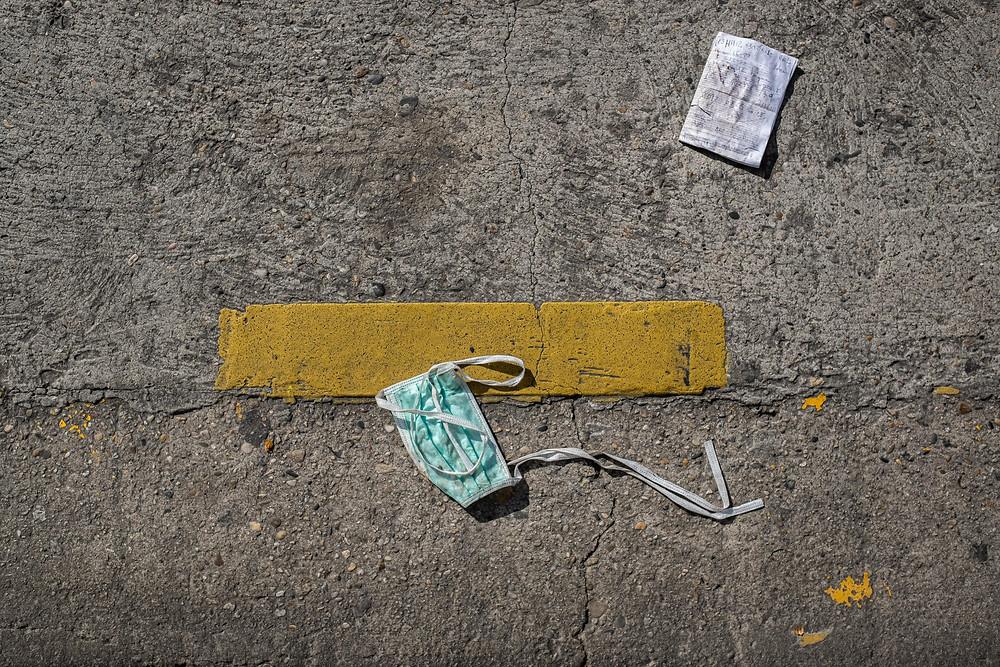 Sebuah masker dan kertas kotor di tengah jalanan