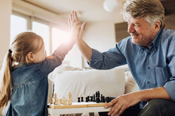 Little girl high fiving grandfather whil