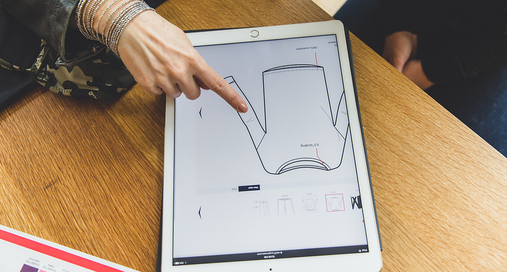 woman pointing at an ipad screen with a drawing of a technical sketch