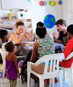 Volunteers teaching english to kids at the neighborhood near the beach