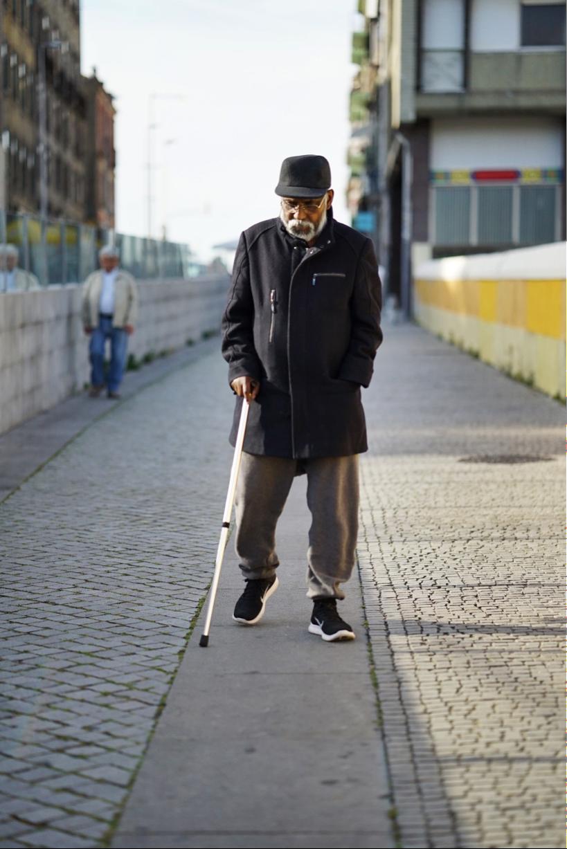 Elderly man walking with cane