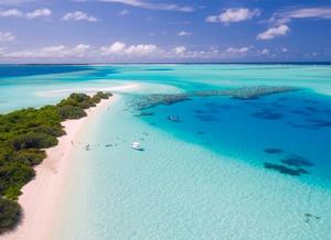 Foto aérea de uma região costeira. A esquerda uma península de terra com vegetação arbórea densa e pequena faixa de areia. Oceano azul claro, com visibilidade boa da água. Vários recifes de corais a direita. No alto da foto, céu azul escuro com nuvens brancas. Perto da costa, um navio e algumas pessoas nesse ambiente natural.
