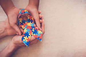 Hands holding puzzle ribbon for World Autism spectrum disorder Awareness Day, pride, jigsa