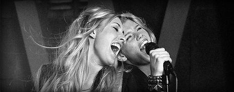 Primo piano di due belle ragazze bionde che cantano a piena gola, sorridenti e felici.