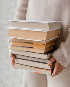 close-up-hands-holding-books-stack.jpg