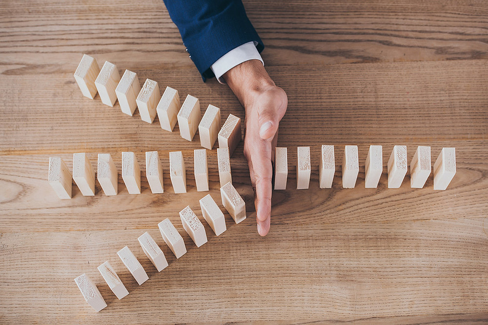 A hand interrupting a row of dominoes falling down
