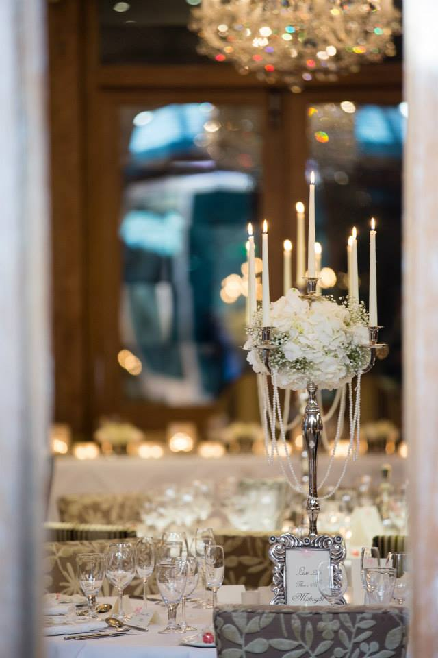 Silver candlestands with dome of white roses, hydrangea and gyp