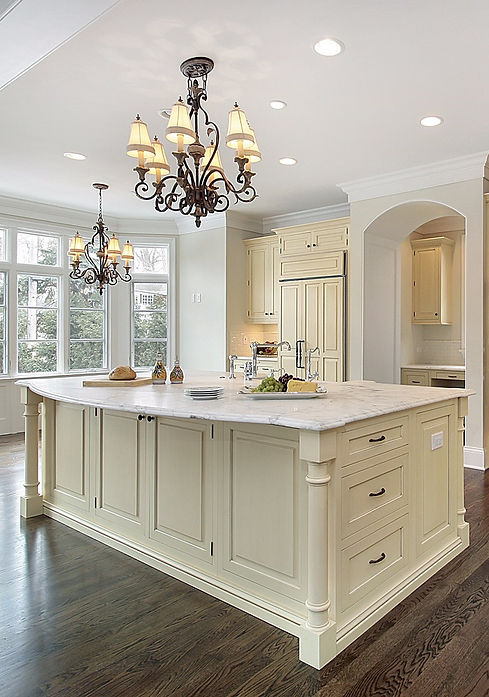 Large Traditional Kitchen with Bay Windows, Island with Custom Cut Marble Countertop with Beveled Curved Edges, Yellow Cabinet Panelled Fridge Doors