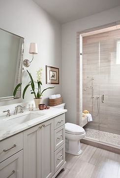 Gray and white bathroom, large tiles in shower with seat, white marble counter, elegant design