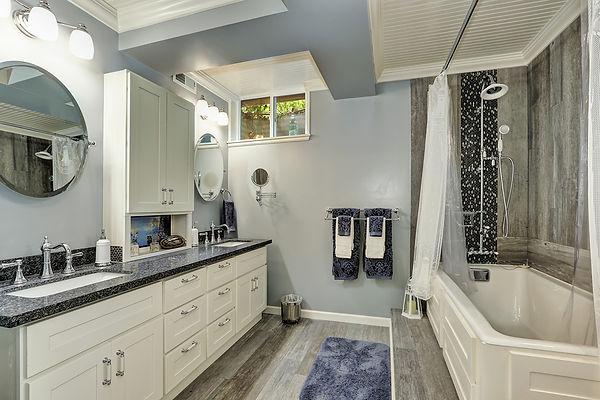 Light Blue Bathroom with Black Granite Countertops & Grey Wood Grain Flooring