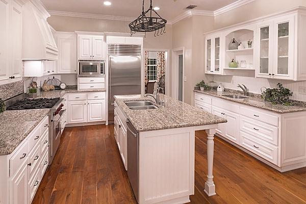 Farmhouse Traditional Kitchen with White Beadboard Backsplash, Open Shelving, Grey & Black Veined Granite Countertop & Walnut Flooring