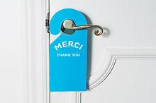 Blue door hanger on white door expressin