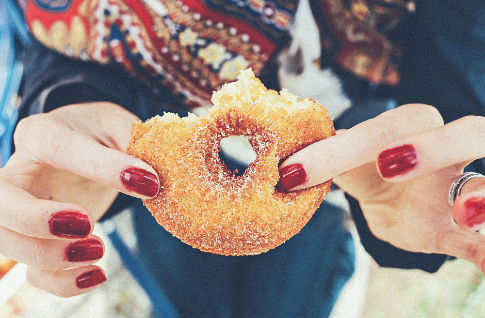 Hands with red painted nails holding half eaten sugary ring doughnut