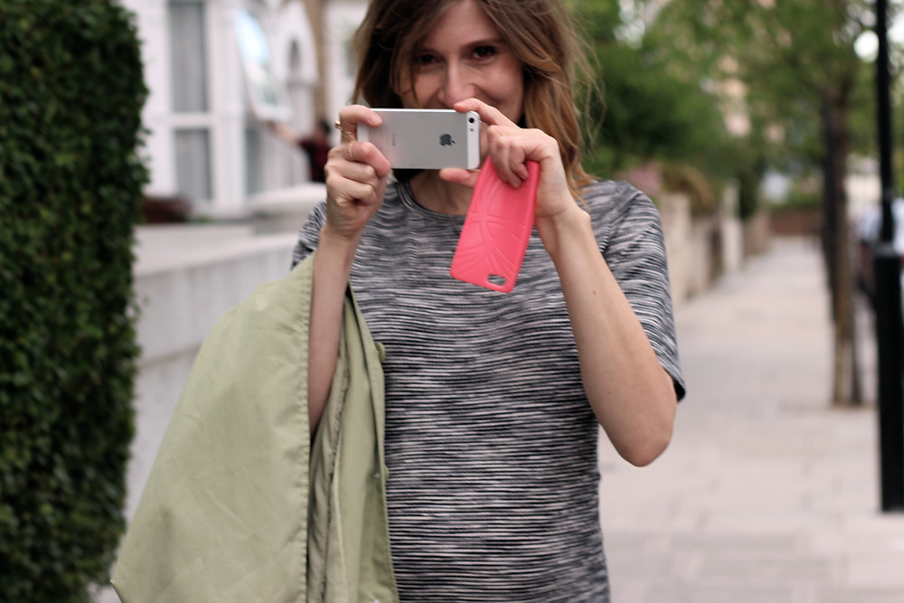 Woman smiling and taking photo with phone