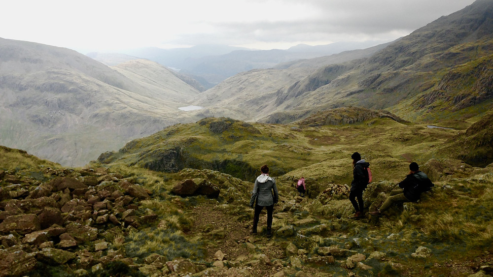 Mountain view over Eskdale with three walkers in foreground