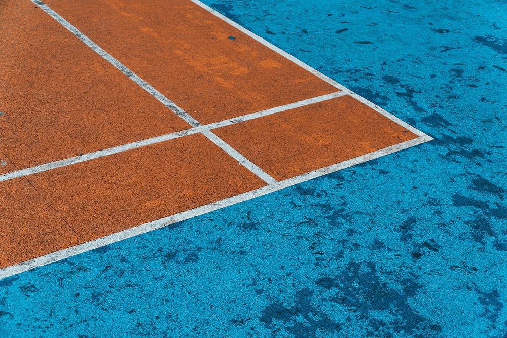 Corner of a blue and orange tennis court