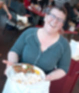 Person happily smiling with a plate of food and potato at Tin Shed on Alberta Street
