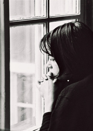 looking pensively through a window without seeing anything