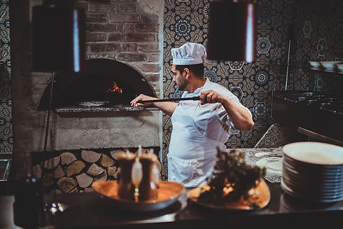 chef-is-putting-pizza-to-the-oven-2TZ42T