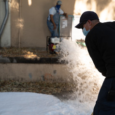 A maintenance worker clears gutters near the South Gym.