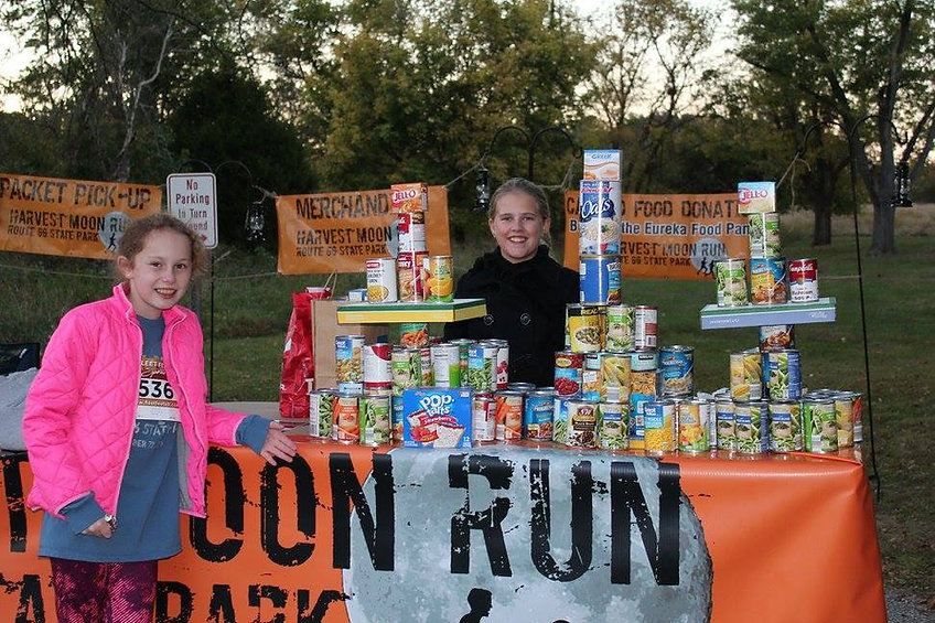 two girls collecting canned goods at the Havest Moon Run