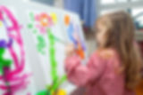 Child in nursery painting a picture of a flower