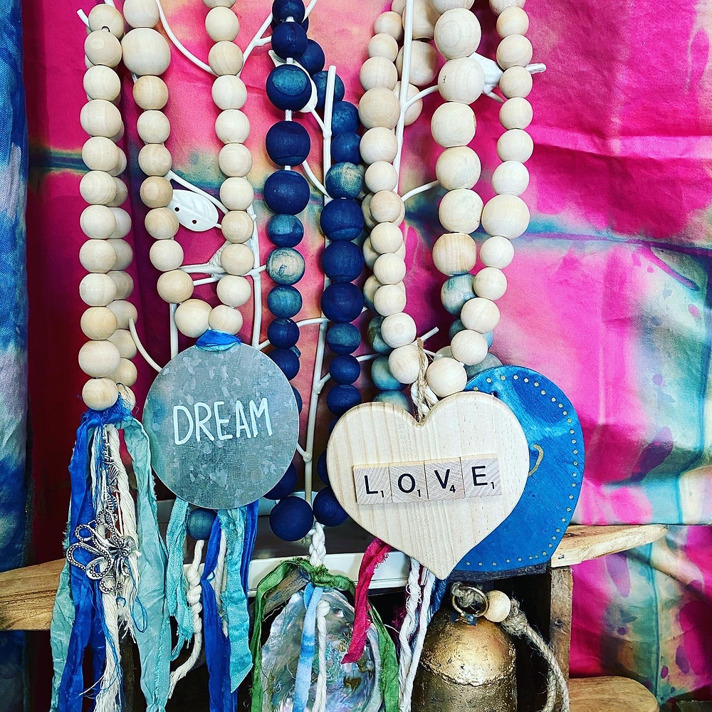 Handcrafted necklaces and beaded decor hang against a dyed-fabric backdrop