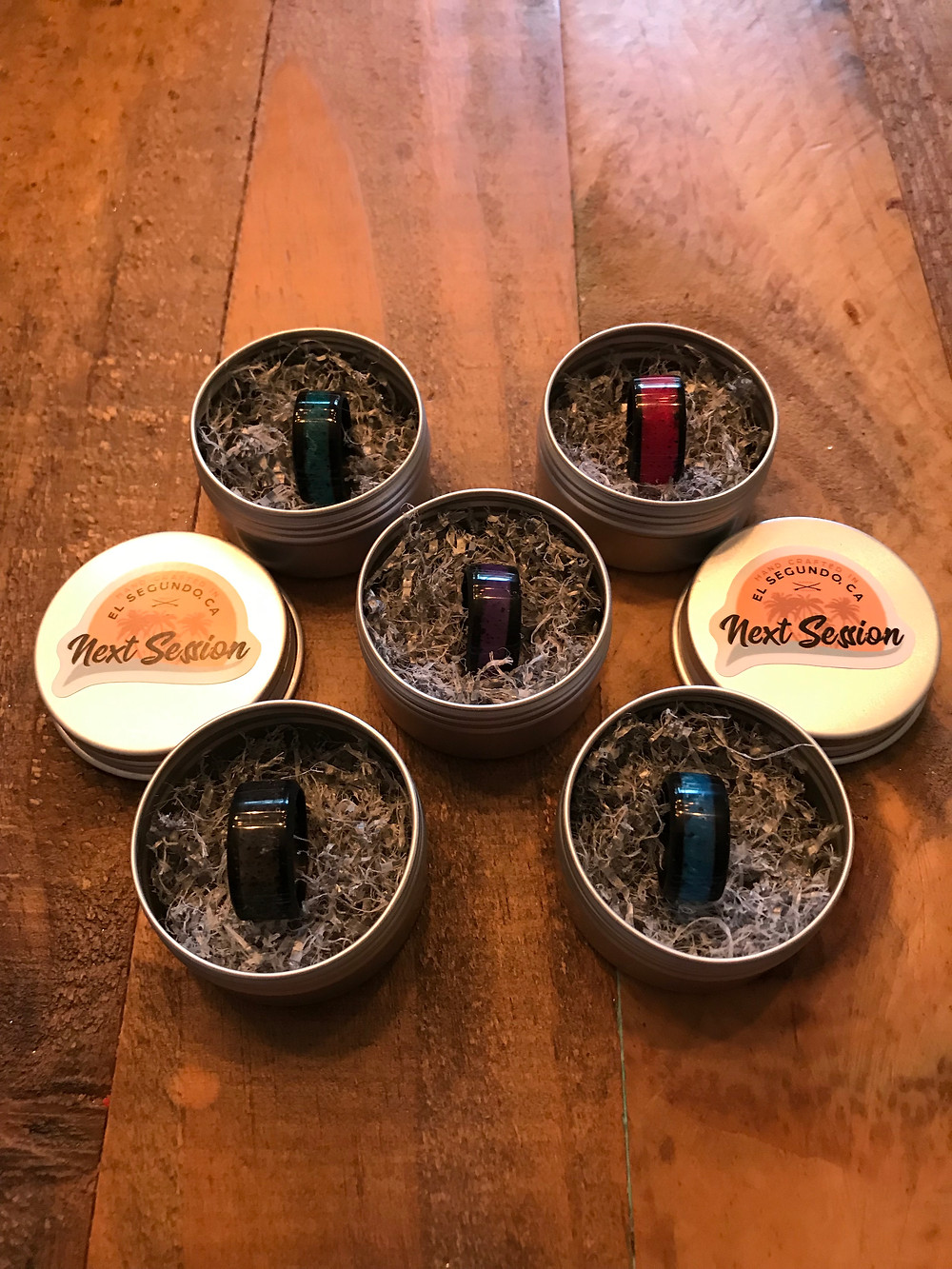 Next Session rings in various colors displayed in their tins