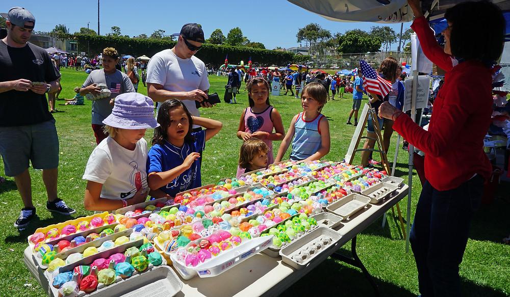 Children peruse confetti eggs at July 4 festivities in El Segundo, CA