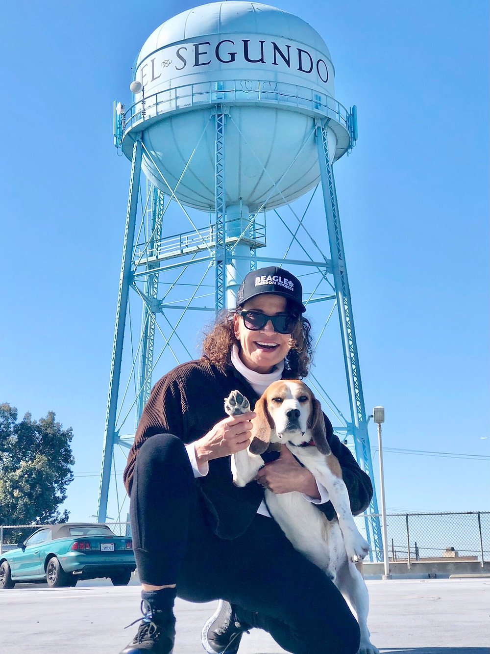 Eileen Bell and her rescue beagle pose in front of El Segundo water tower