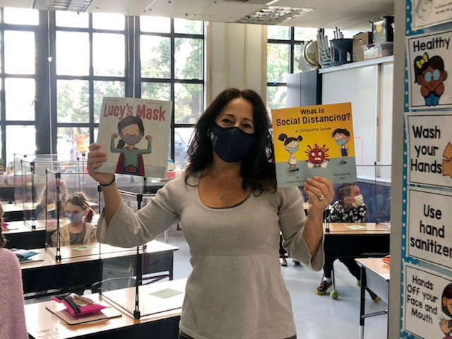 Teacher Alisa Lister stands in her classroom holding two picture books about the coronavirus pandemic.