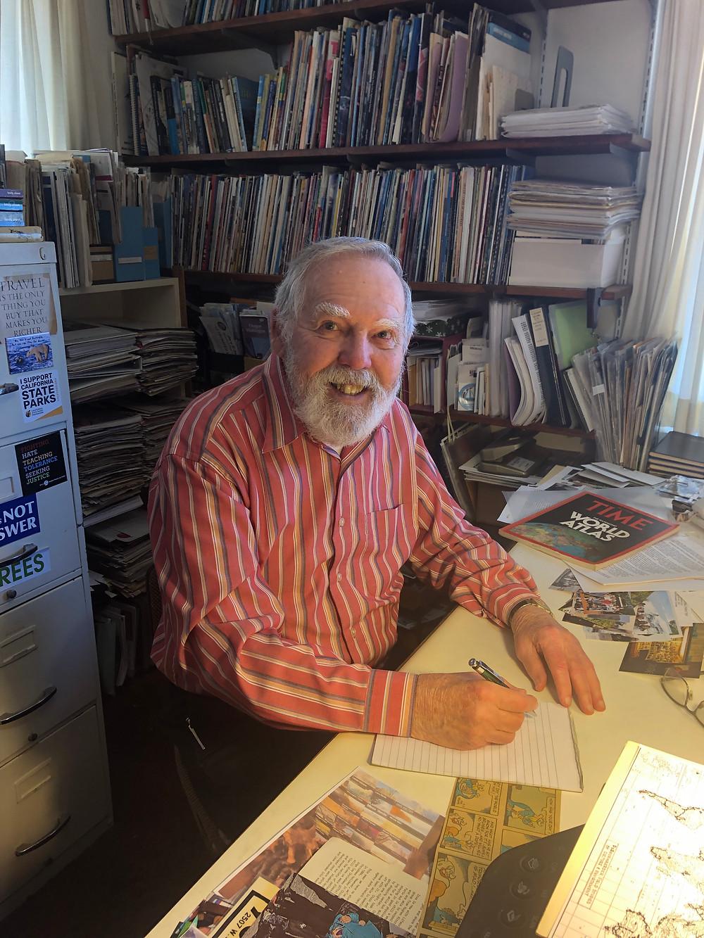 Chuck deDeurwaerder sits in his home office