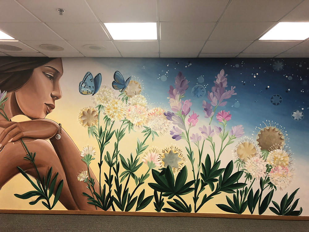 A mural by Nanibah Chacon featuring an indigenous woman looking at native flora and cog stones