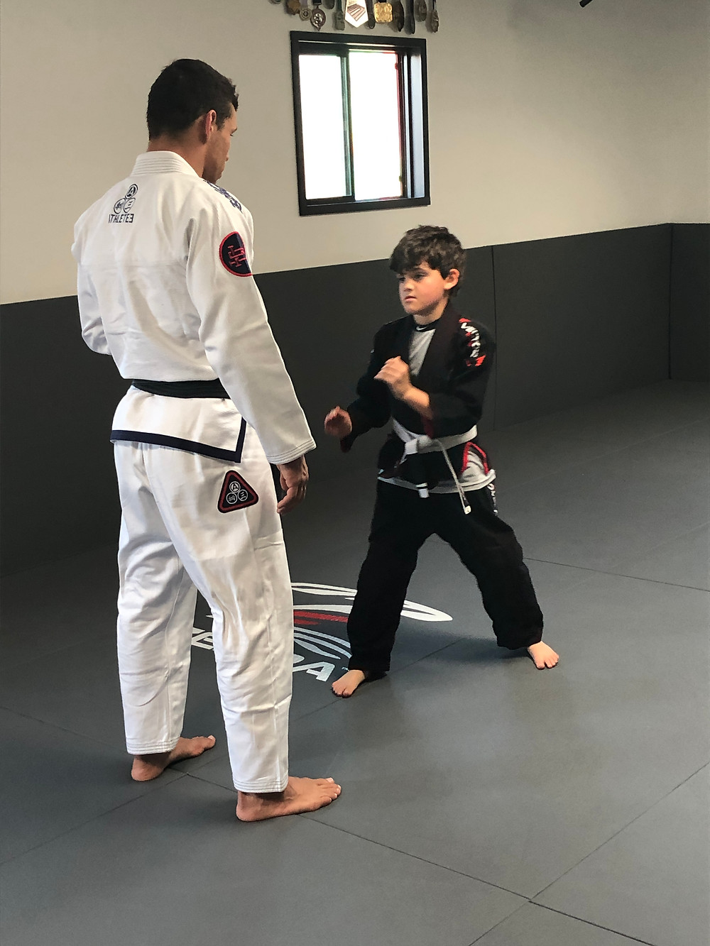 Brazilian Jiu-Jitsu professor Thiago Rodrigues instructs a young student