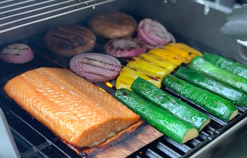 Salmon, burgers, and various colorful vegetables cooking on a grill.