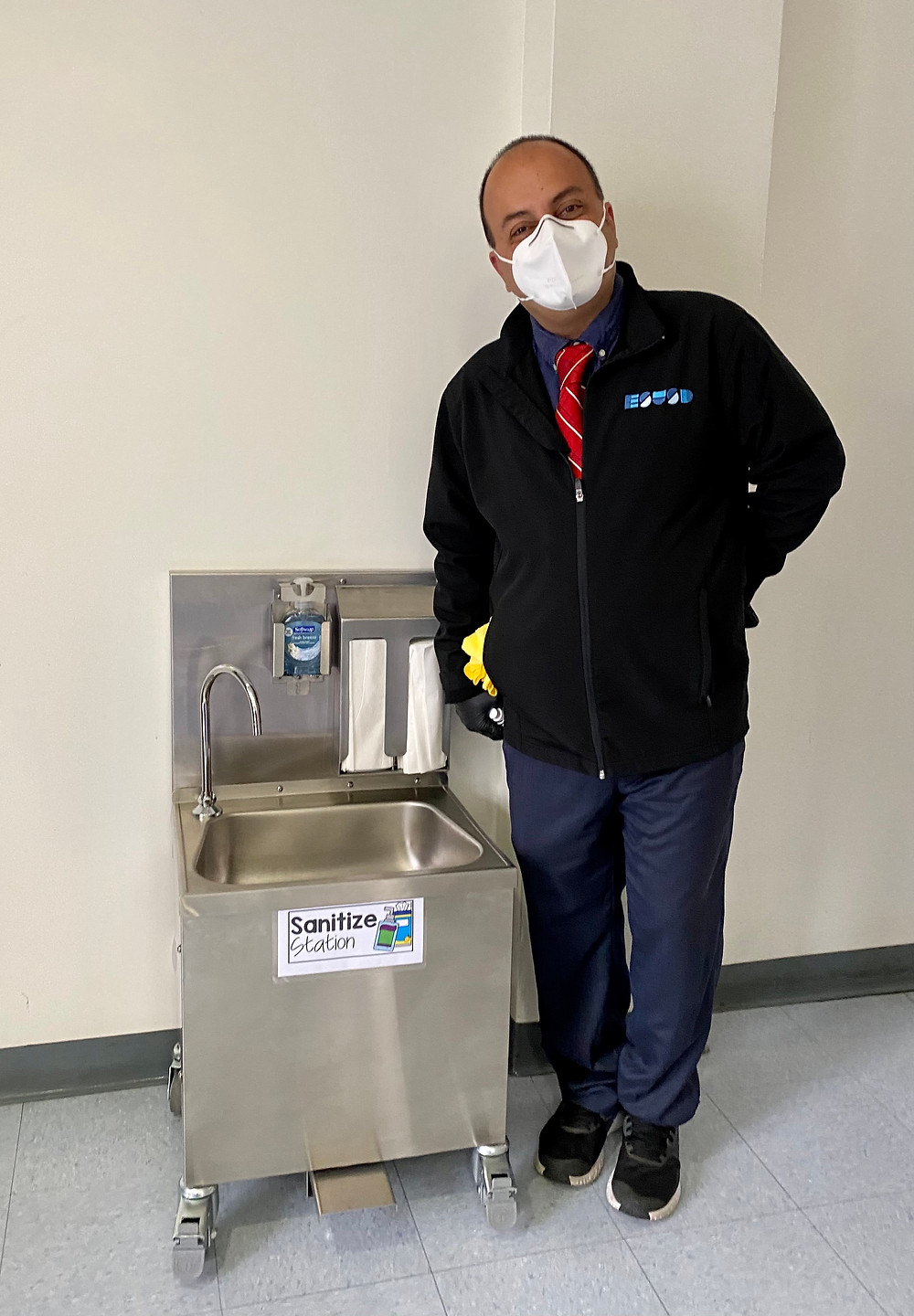 Ali Rabiei poses next to a scaled-down hand-washing station for kindergarten students.