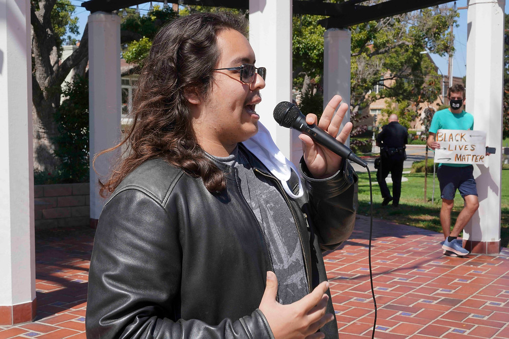 Elias Garcia speaks at microphone in Library Park in El Segundo California