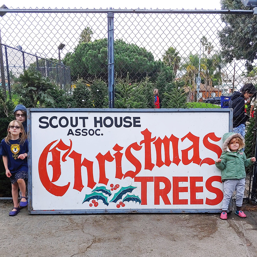 Children flank the El Segundo Scout House Tree Lot sign in front of the Christmas Tree Lot