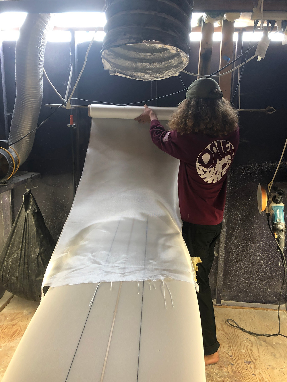 Grayson Daley rolls out fiberglass for application to a surfboard