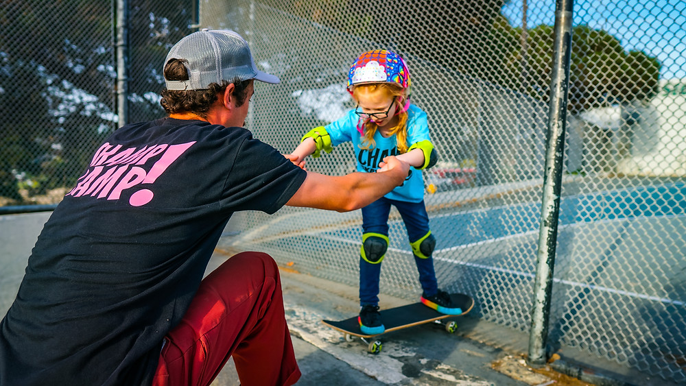 A skating instructor helps a child learn to skate