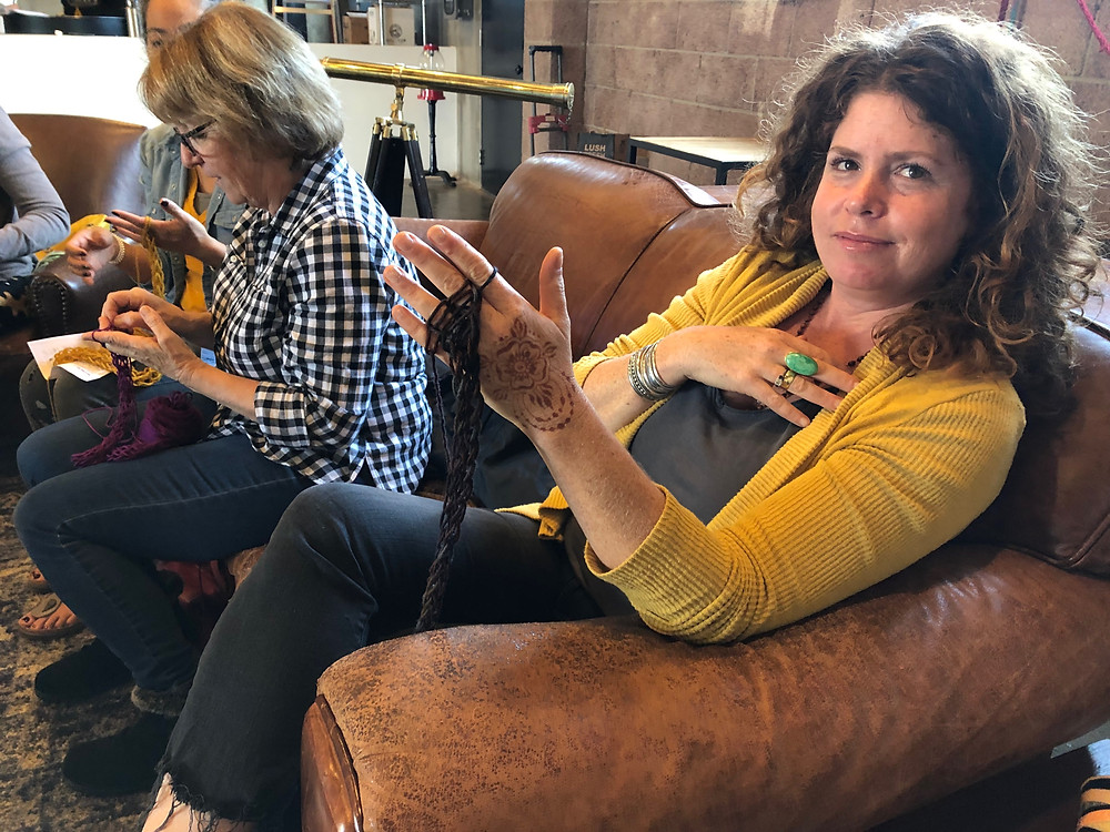 Women finger-knit on a sofa in a coffee shop in El Segundo, California