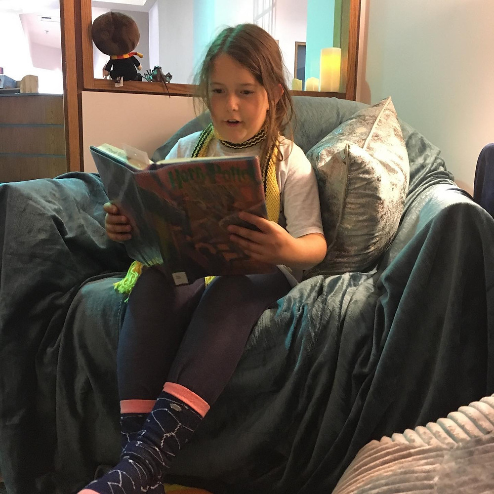 Margot Strong sits in a comfortable armchair reading aloud from a Harry Potter novel