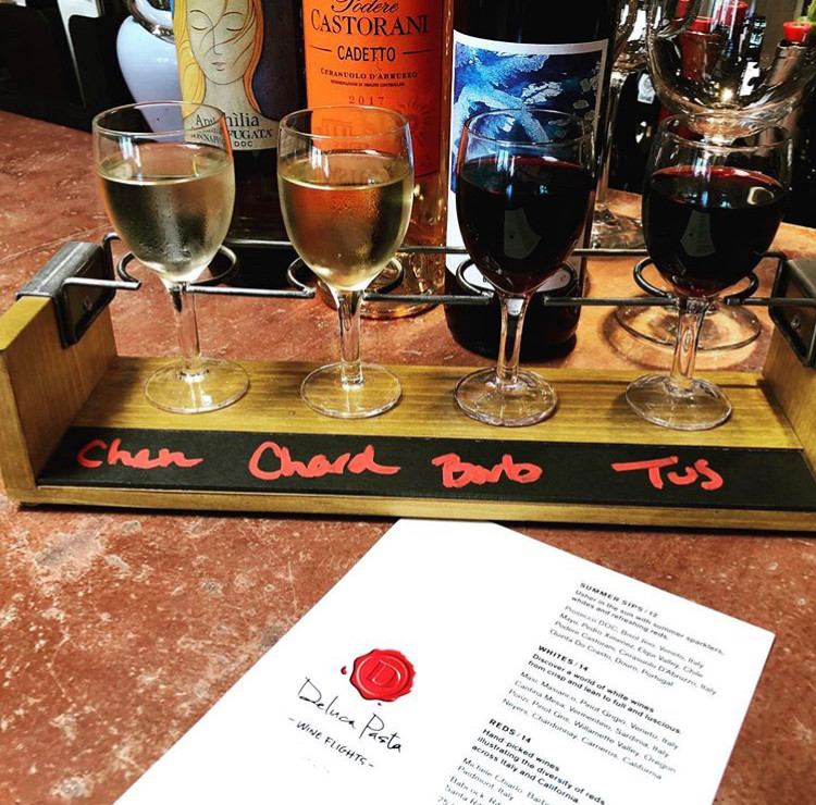 Four glasses of wine in a flight tray