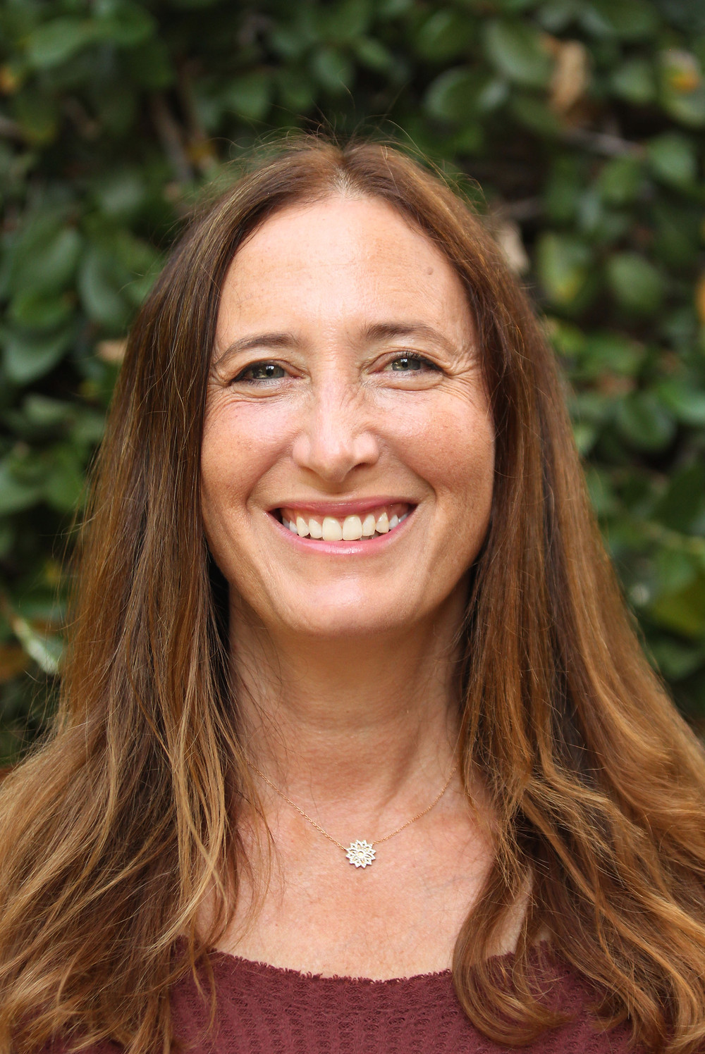 Headshot of Sherri Cadmus with a greenery background