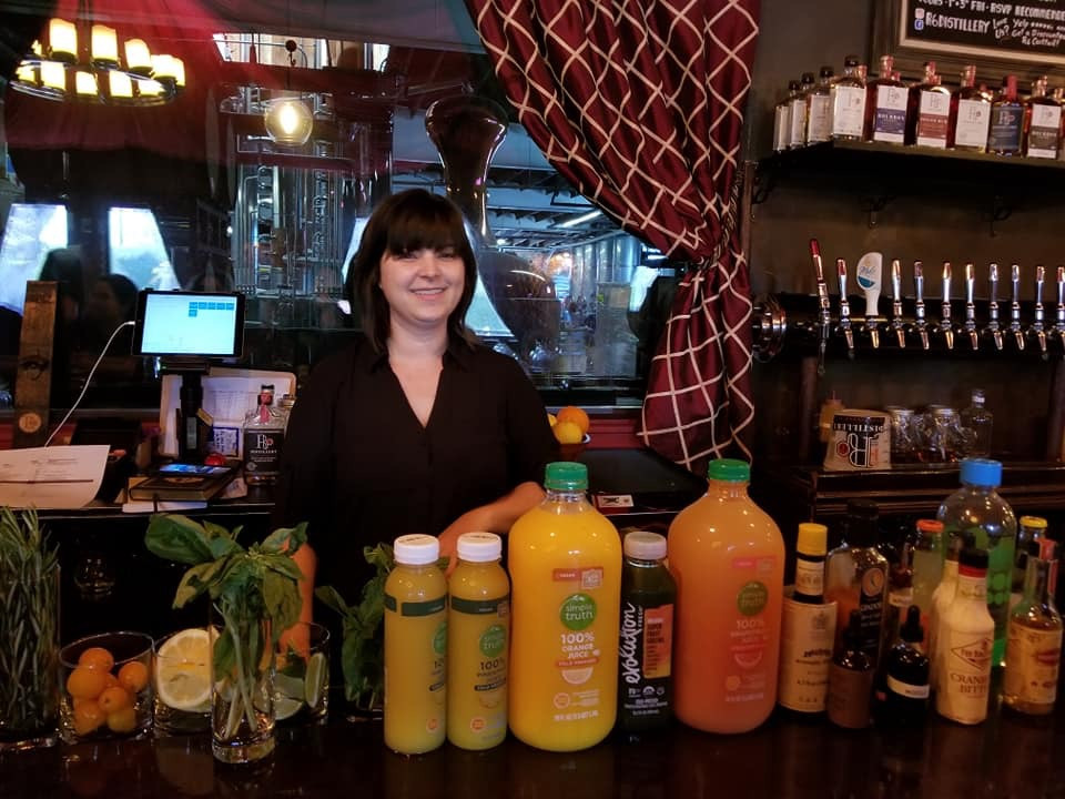 Meredith Hayman poses with cocktail ingredients behind a bar