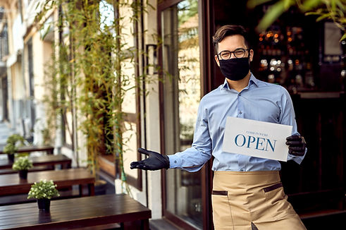 Happy waiter with protective face mask h