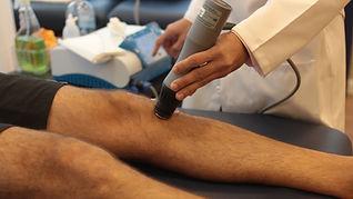Fisioterapeuta Edson Santiago aplicando tratamento de ondas de choque em paciente