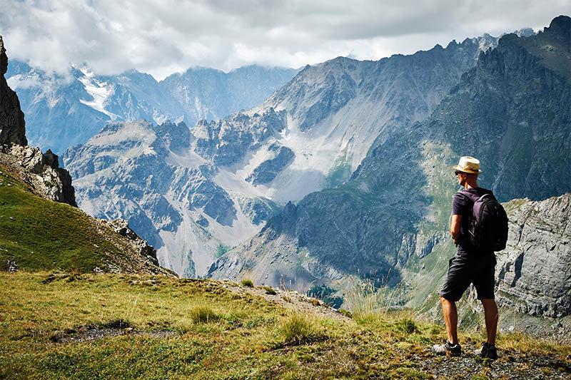 Homem observando montanha ao fundo