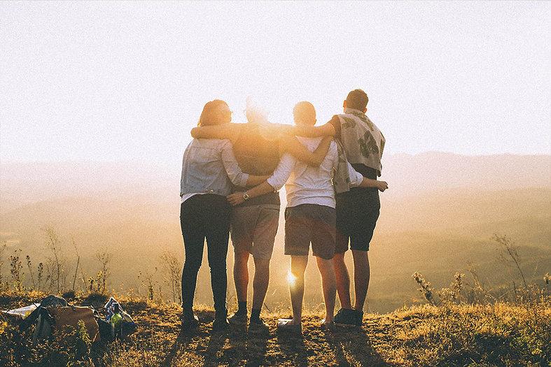 Grupo de pessoas se abraçando olhando o Sol se por