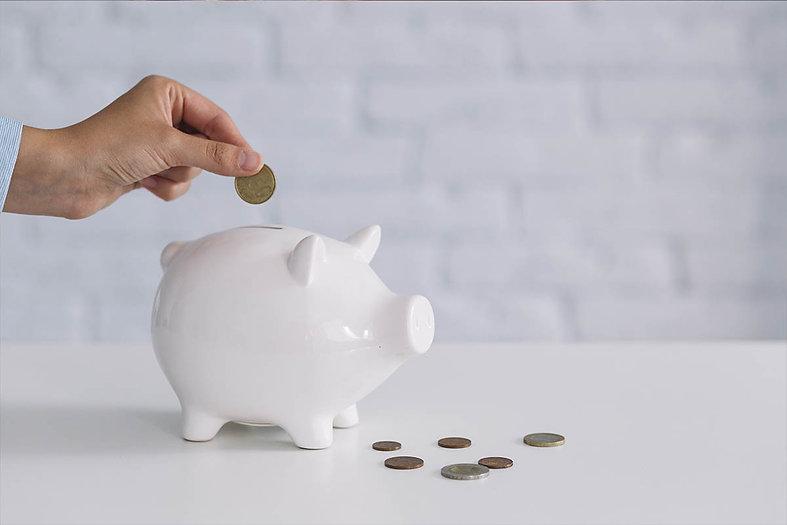 Homem colocando uma moeda em um porquinho banco
